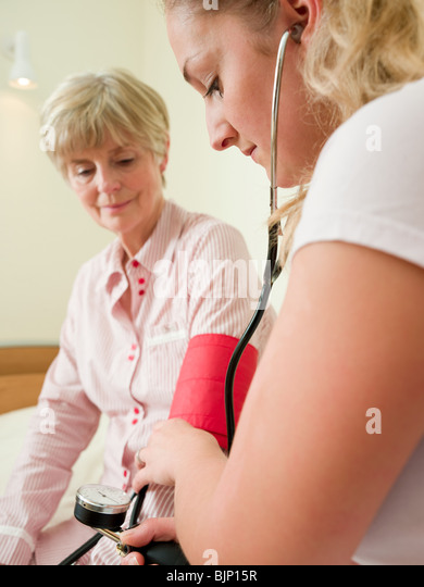 Senior woman having her blood pressure checked - Stock Image