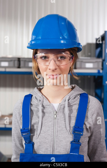 Germany, Neukirch, Young woman wearing hardhat and safety glasses, portrait - Stock Image