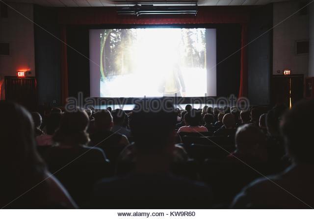 People watching movie in dark movie theater - Stock Image