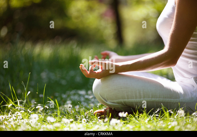 A young woman meditating outside, close up of hands - Stock Image
