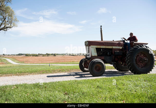 Farmer driving tractor on rural road, Missouri, USA - Stock Image