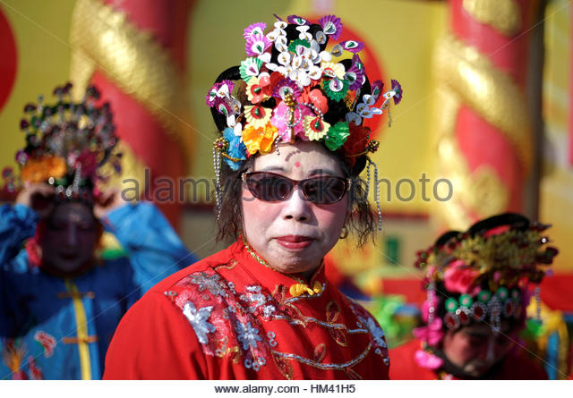 A folk artist waits to perform for a temple fair at Badachu park as the Chinese Lunar New Year, which welcomes the - Stock-Bilder