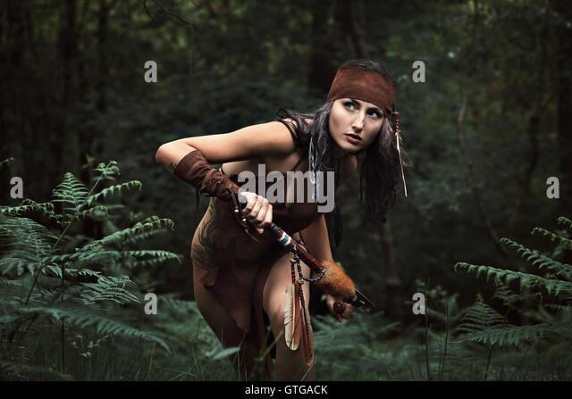 Beautiful indian huntress in a green forest . Native warrior - Stock-Bilder