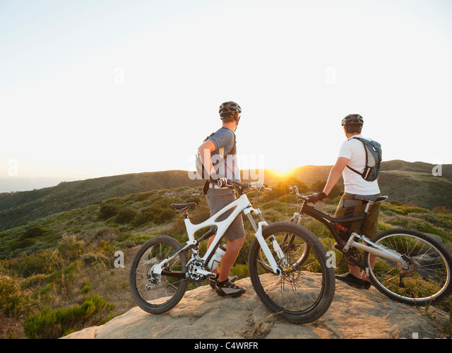 USA,California,Laguna Beach,Two bikers on hill looking at view - Stock-Bilder