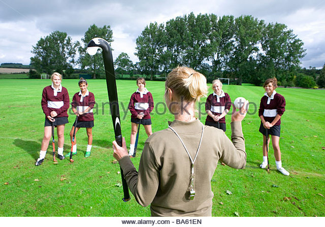 Coach holding field hockey stick and ball in front of team - Stock Image