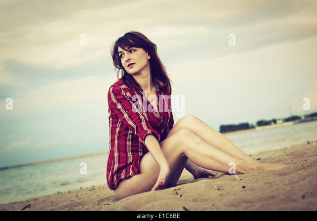 Young woman in a red checked shirt relaxing on the beach at sunset - Stock Image