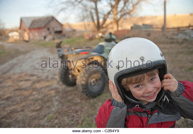 A young boy wearing a protective helmet on a farm in Dunbar, Nebraska. - Stock-Bilder