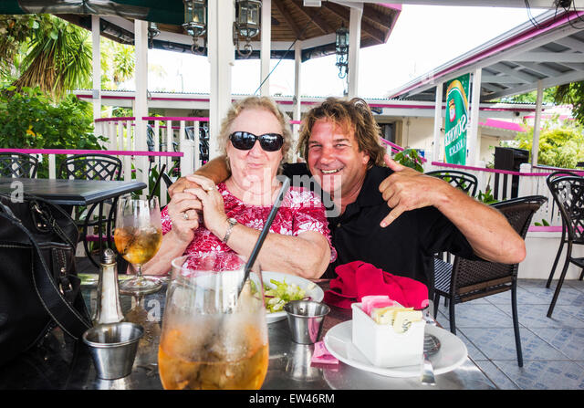 A 78 year old Caucasian woman is embarassed by a stranger's hug on the patio of a beachside cafe. St. Croix, - Stock Image