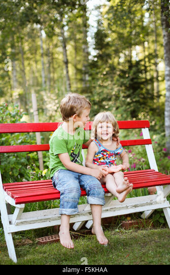 Sweden, Narke, Hallsberg, Boy (4-5) and girl (2-3) sitting on bench - Stock Image