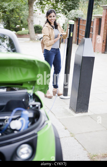 Woman charging electric car on street - Stock Image