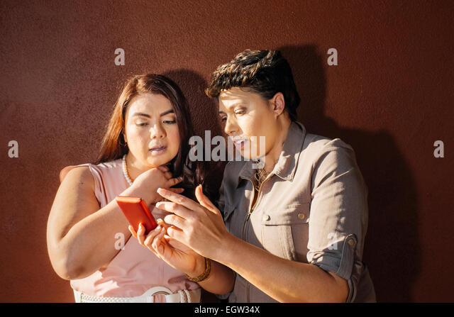 Two friends looking at cell phone. - Stock Image