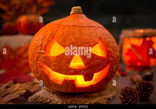 Burning Jack O'Lantern on a rustic table with autumn decorations, darkly lit. - Stock Image