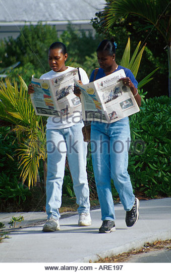 Bahamas Elbow Cay Hope Town women read The Abaconian newspaper after ferry ride - Stock Image