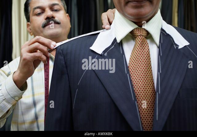 Tailor measuring business man with tape measure, close up - Stock-Bilder