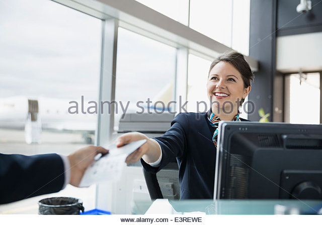 Airport customer service representative giving ticket to traveler - Stock Image