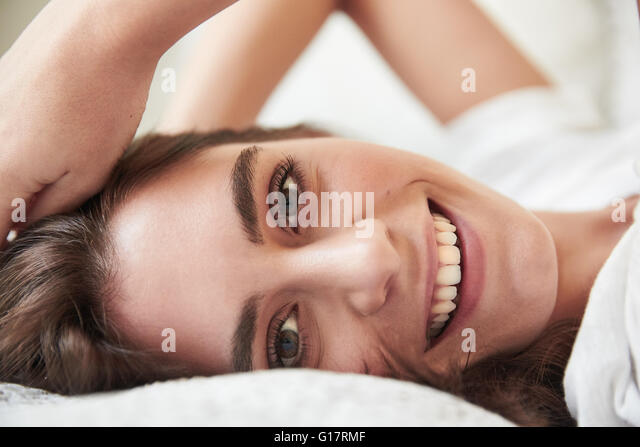 Close up portrait of beautiful young woman lying on bed - Stock Image