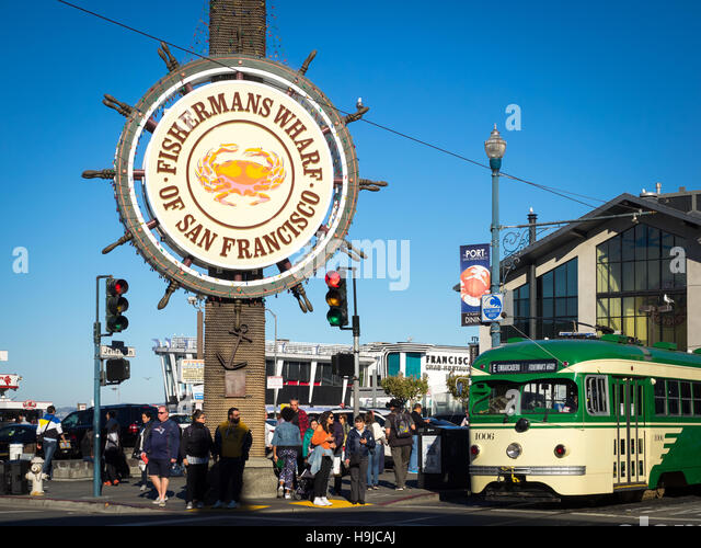 A view of the famous Fisherman's Wharf sign, with an F-line streetcar in front,  in San Francisco, California. - Stock Image