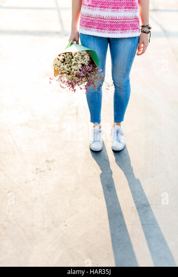 Young Woman Holding Flowers Concept - Stock Image