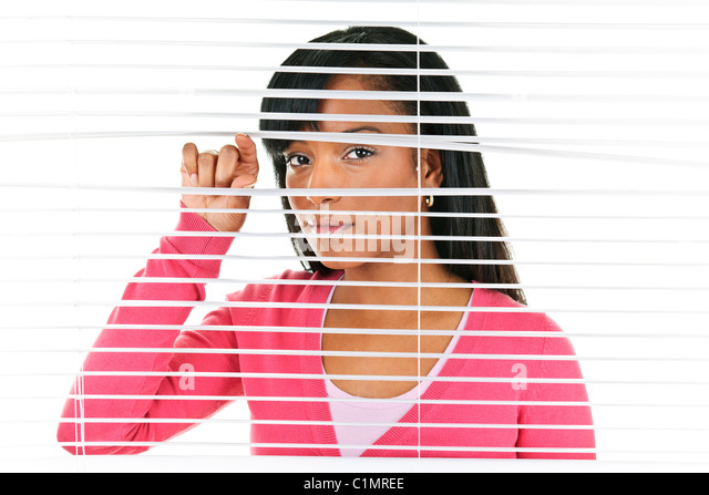 Young black woman looking through horizontal venetian blinds - Stock-Bilder