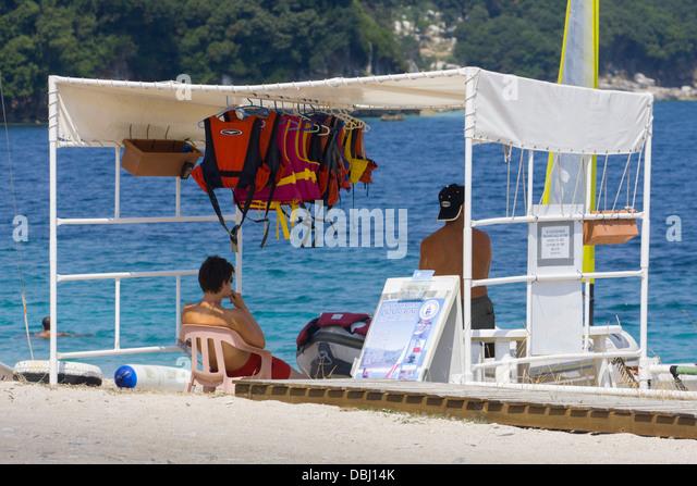 Wind-surfing instructors under shade on Avlaki beach Corfu - Stock Image