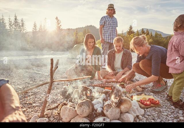 Family sitting around campfire preparing food - Stock-Bilder