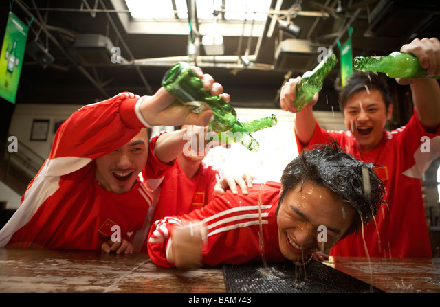 Young Men Pouring Alcohol Over Young Man Leaning On Bar - Stock Image