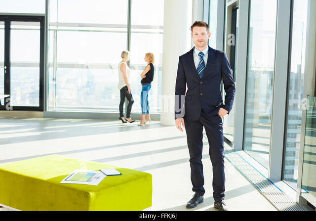 Well-dressed businessman with colleagues in background - Stock Image