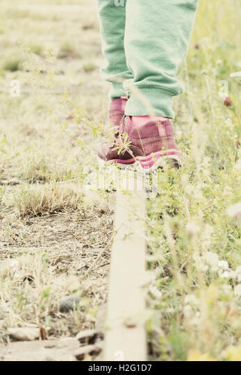 Little girl walking on old railroad tracks. Summer lifestyle image of childhood. Grass and flowers growing by the - Stock-Bilder