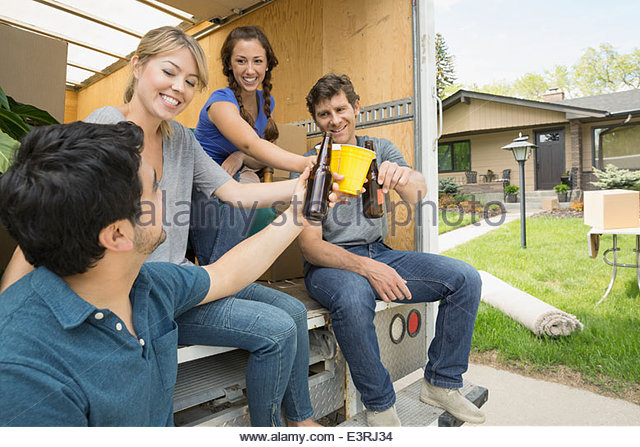 Couples toasting beer at back of moving van - Stock Image