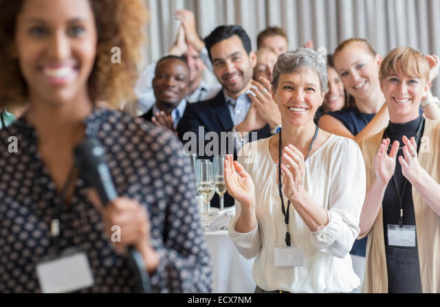 Group of people applauding after speech during conference - Stock Image