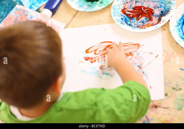 Preschool kid finger painting - Stock Image