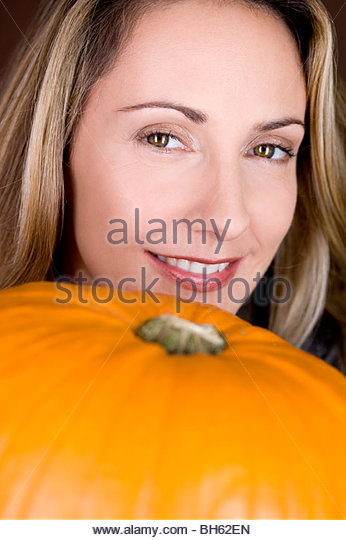 A mid adult woman with a pumpkin - Stock Image