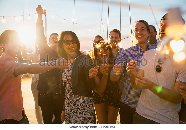 Friends with sparklers enjoying party - Stock Image