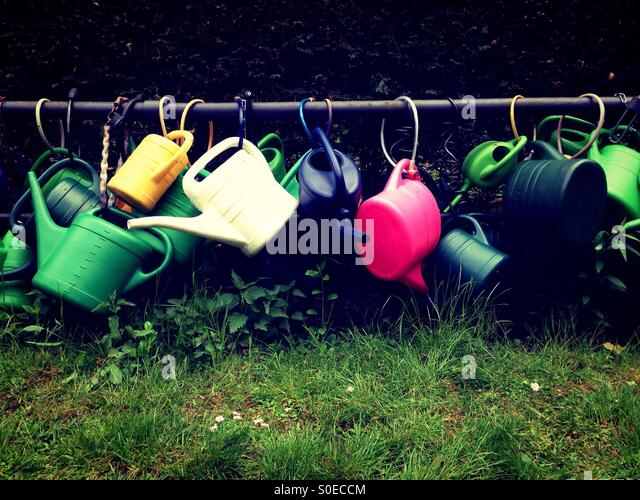 Plastic Watering cans attached to a metal bar on a cemetery in Berlin Kreuzberg - Stock-Bilder