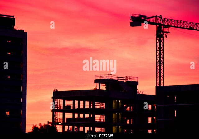 Building under construction at dusk. - Stock Image