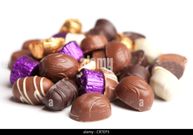 A selection of chocolates in an untidy pile against a white background - Stock Image