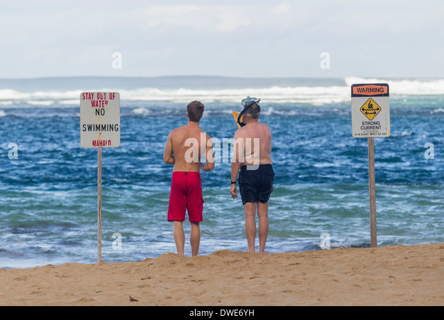 Tunnels Beach, Kauai, Hawaii, USA - Two swimmers deciding whether to swim in treacherous winter waters - Stock Image