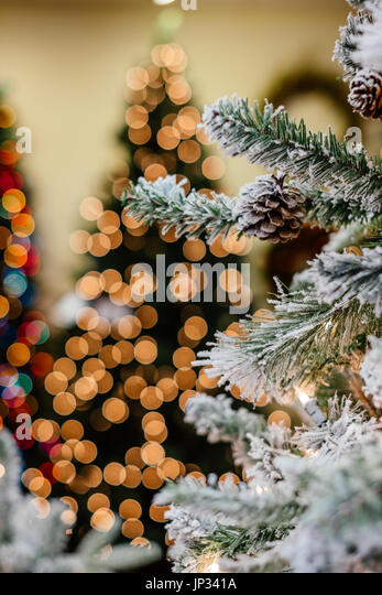 Traditional Christmas decorations on display in a retail shop showing shallow depth of field and lighted Christmas - Stock Image
