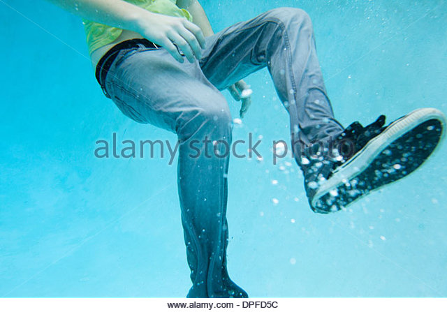 Close up of male legs full clothed underwater - Stock Image