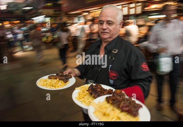 Waiter serving steak and fries, Parilla type restaurant, Mercado del Puerto, Montevideo, Montevideo, Uruguay - Stock Image