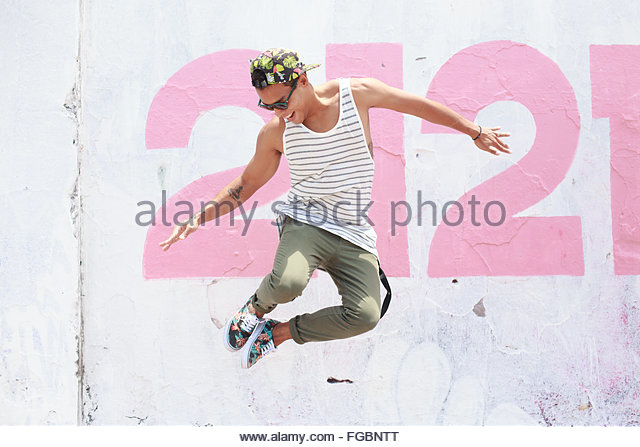 Happy Young Man Jumping Against Wall - Stock Image