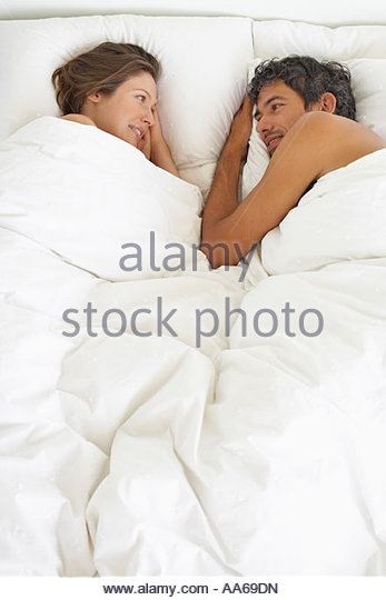 Woman and man lying down in bed - Stock-Bilder