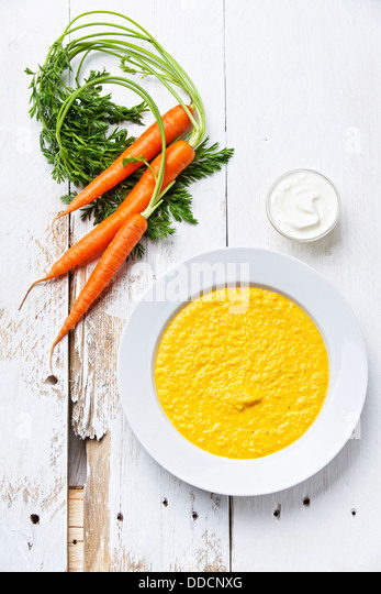 Carrot soup on white wooden background - Stock Image