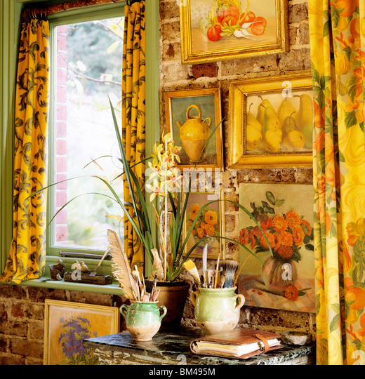 Detail of artwork and table display with daffodils and paintbrushes in confit jars. - Stock Image