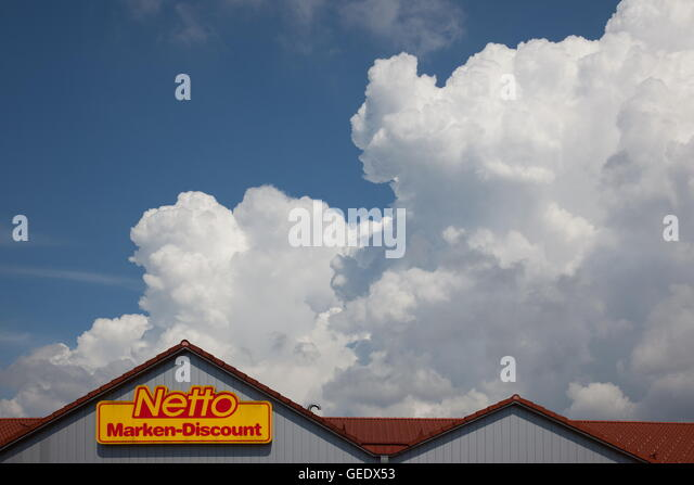 Roof and facade of a Netto Marken-Discount Supermarket and storm clouds. Bavaria, Germany, Europe. Photo by Willy - Stock Image