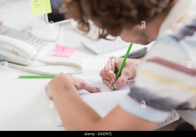 Young creative drawing plans at desk, close up - Stock-Bilder