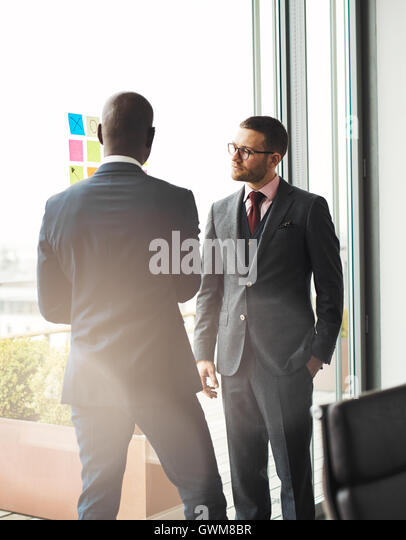 Serious young businessman wearing glasses standing in front of a bright window overlooking a patio talking to an - Stock Image