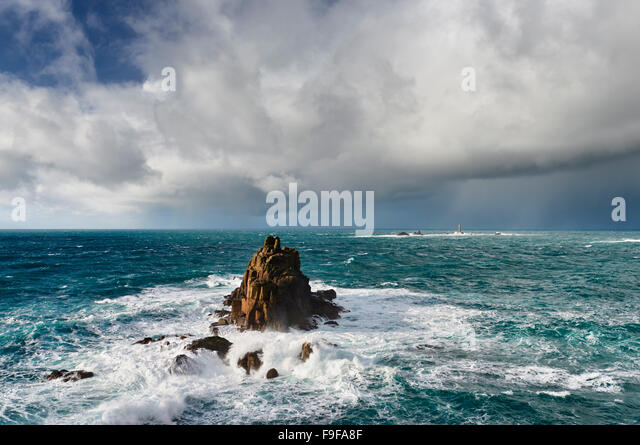 Huge seas crash around the Armed Knight rock formation at Lands End Cornwall - Stock Image