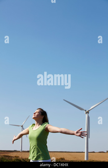 Young woman mimicking wind turbines - Stock Image