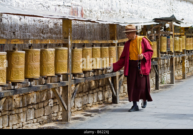 Tibetan monk holding beads and spinning prayer wheels along the road below the Potala Palace, Lhasa, Tibet. JMH3750 - Stock Image